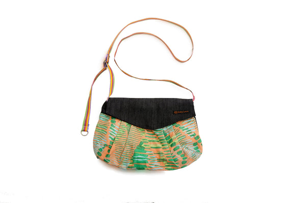Vibrant orange and green geometric shapes with rainbow strap. Upcycled handmade cotton purse bag with zipper closure. Sustainable, fair trade, ethically produced. Empowers women in Brazilian favela slums in Rio de Janeiro.