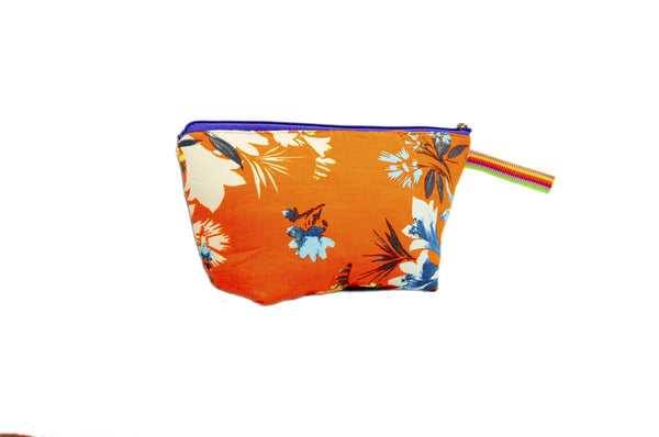 Vibrant orange with blue and creme flowers. Upcycled handmade cotton clutch bag with zipper closure. Sustainable, fair trade, ethically produced. Empowers women in Brazilian favela slums in Rio de Janeiro.