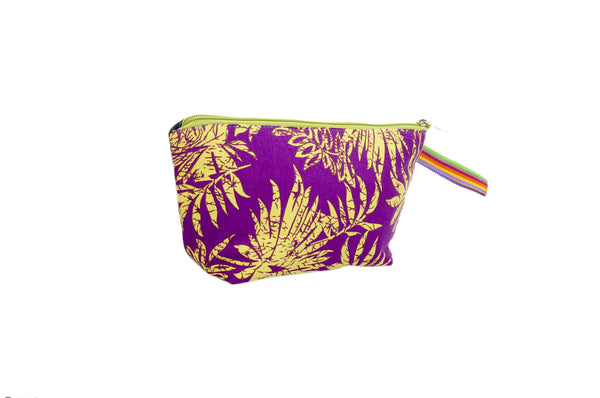 Smoky purple background with vibrant yellow flowers. Upcycled handmade cotton clutch bag with zipper closure. Sustainable, fair trade, ethically produced. Empowers women in Brazilian favela slums in Rio de Janeiro.