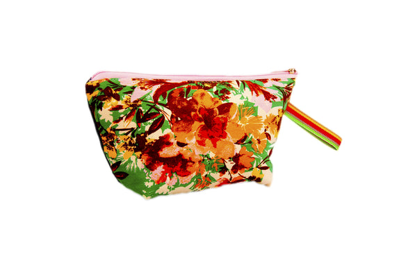 Large smattering of vibrant flowers. Upcycled handmade cotton clutch bag with zipper closure. Sustainable, fair trade, ethically produced. Empowers women in Brazilian favela slums in Rio de Janeiro.