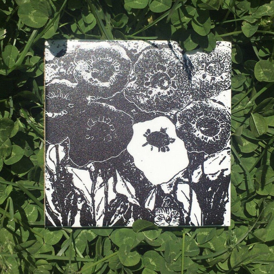 Ceramic tile coaster. Poppies and cat. Image of top black and white floral with cat coaster. Vitrene by Christine and Bruce Green. Pottery and artwork from Micanopy Florida.
