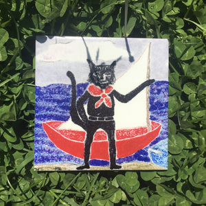 Ceramic tile coaster. Cat and sailboat. Top image. Vitrene by Christine and Bruce Green. Pottery and artwork from Micanopy Florida.