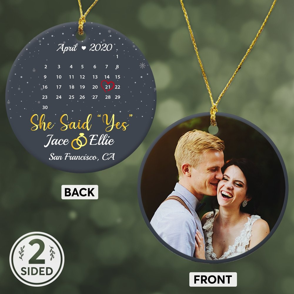 """If she likes something small and meaningful. Let get her a love custom ornament. An ornament with your favorite photo and the date """"She said yes"""", will help you say everything. Anniversary gifts for a wife don't need to be huge or expensive, it just needs to show enough meaning."""