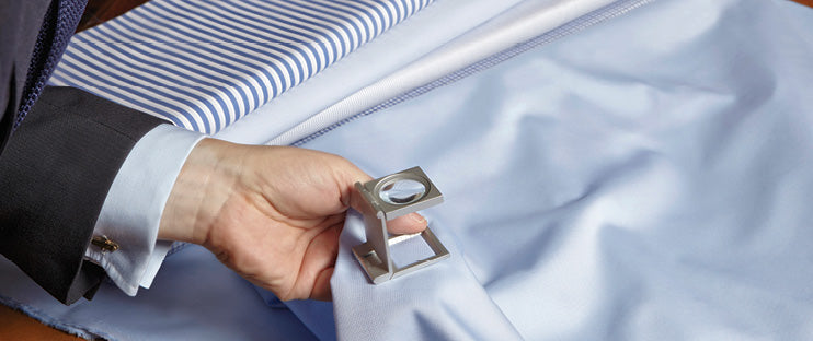 Tailor examining shirt with loupe