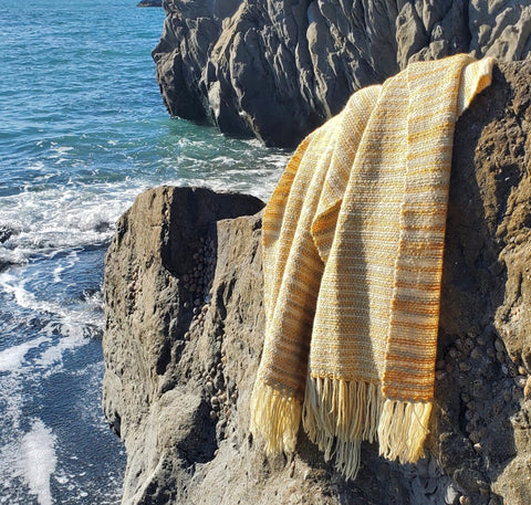 handwoven yellow shawl on a rock. ocean and more rocks in the background