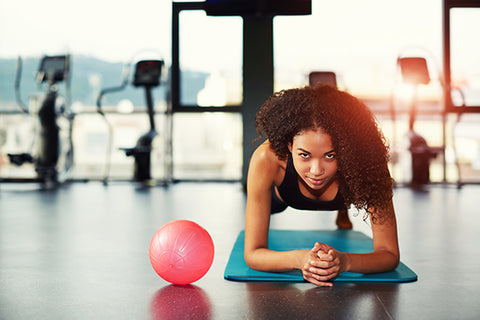 Woman does a plank on an exercise mat
