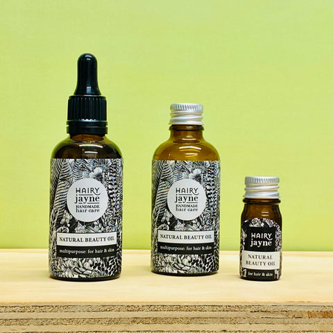 natural beauty oil in 3 different bottles, one with pipette, one with aluminium cap, one sample size
