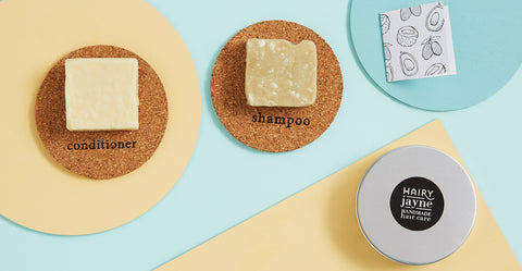 shampoo and conditioner bar with on cork resting mats with travel tin.flat lay image on pastel coloured background