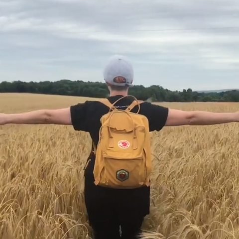 jayne in a field of wheat wearing a ruck sack and cap