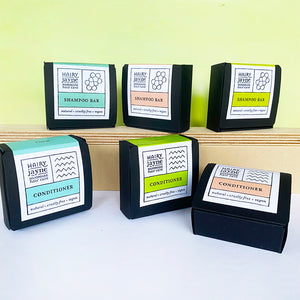 6 assorted solid shampoo and conditioner bars in their recyclable cardboard boxes