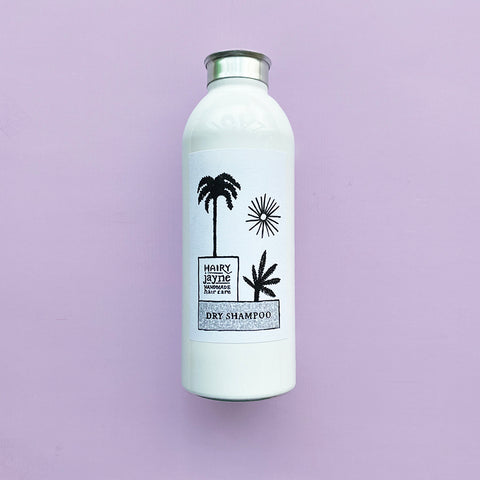 dry shampoo in a white aluminium talc bottle, a palm tree, sun and plant on the label