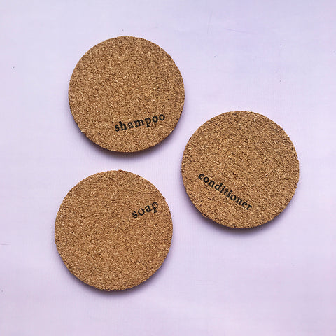 3 circular mats made from cork, they are stamped with the words shampoo, conditioner and soap
