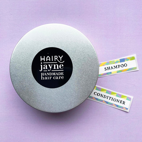 round aluminium travel tin for solid bars with hairy jayne logo and additional stickers for labelling shampoo or conditioner