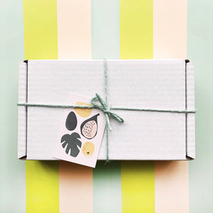 our gift wrap - a white cardboard box tied with mint twine with a card for gift message. the card has illustrations of fruit and a palm leaf