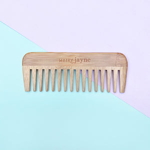 bamboo detangling comb with wide teeth and hairy jayne logo engraved into it