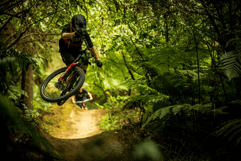 MOUNTAIN BIKER CATCHES AIR OFF A ROLLER IN THE WOODS