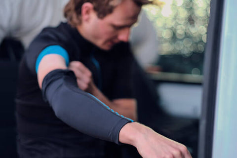 CYCLIST PUTTING ON ARM WARMERS