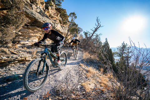 MOUNTAIN BIKERS ON EXPOSED CLIFF