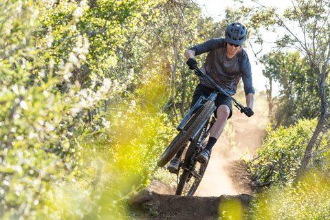 MOUNTAIN BIKER CATCHING AIR SURROUNDED BY WILD FLOWERS