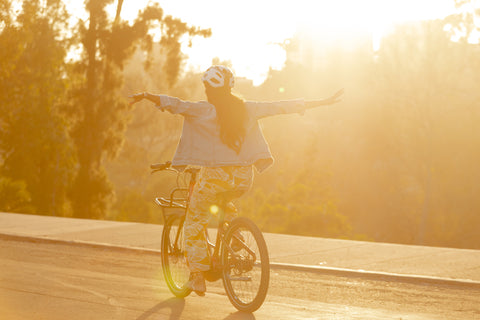 Woman riding bike with no hands at sunset.