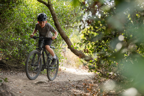 YOUNG MOUNTAIN BIKER IN THE WOODS