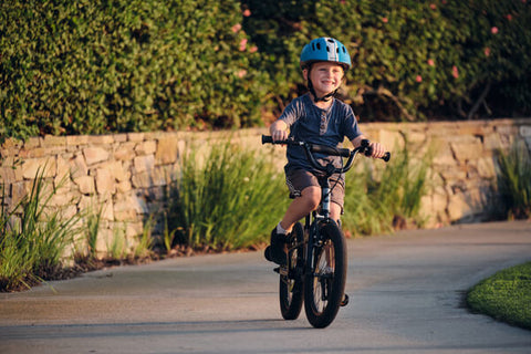 KID RIDING BIKE WITH HUGE GRIN ON FACE