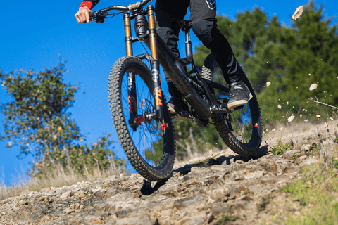 MOUNTAIN BIKER THROWING ROCKS FROM REAR TIRE