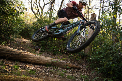 MOUNTAIN BIKER CATCHING AIR OVER A DOWNED TREE