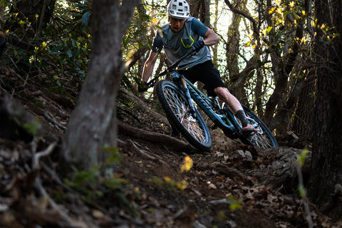 MOUNTAIN BIKER CUTTING THROUGH THE FOREST