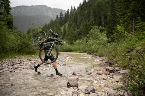 CYCLIST CARRYING CROSSBIKE OVER STREAM