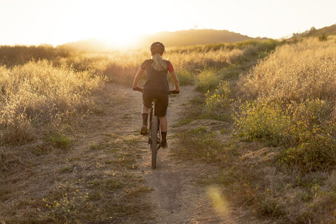 MOUNTAIN BIKER RIDING INTO THE SUNSET