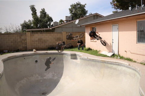 BMX RIDER AIRING OUT OF EMPTY SWIMMING POOL