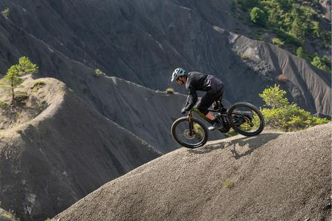 MOUNTAIN BIKER ON THE REIGN E+ DROPPING SCENIC RIDGELINES