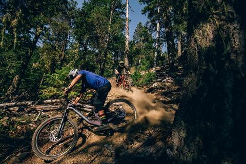 MOUNTAIN BIKERS MAKING TIGHT TURNS OFF ROAD