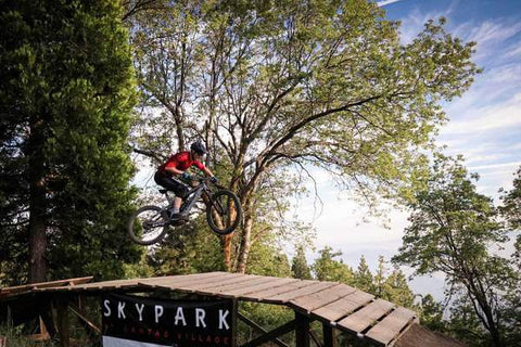 MOUNTAIN BIKER AIRS OVER A WOOD JUMP AT SKYPARK