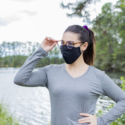 Young woman wearing glasses with the black smart pro mask using the fog guard.