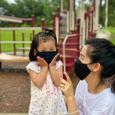 Woman and child both wearing the black Smart Pro Mask using the fog guard.