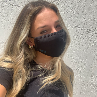 Adult female wearing the black Smart Pro Mask with fog guard down.