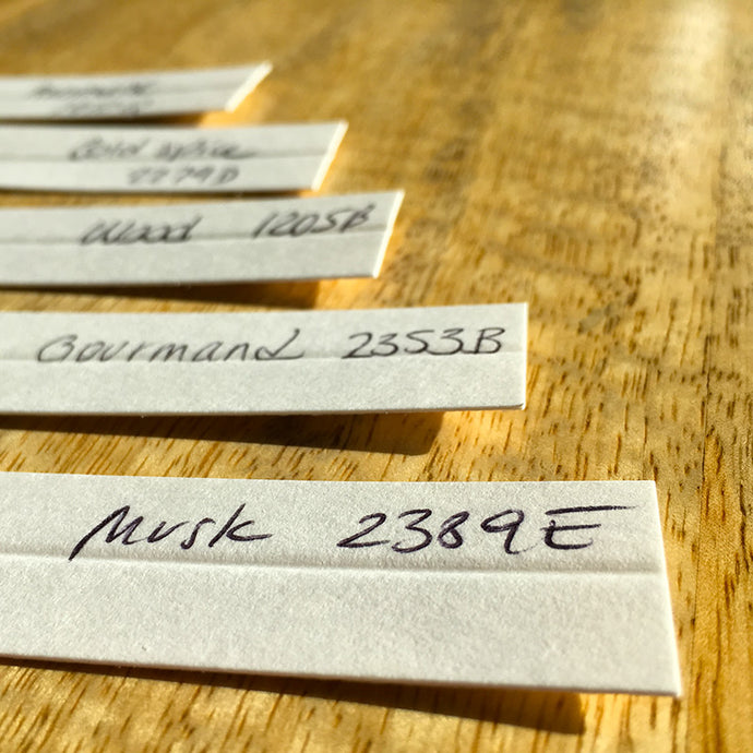 set of fragrance blotters with handwritten labels showing musk gourmand wood