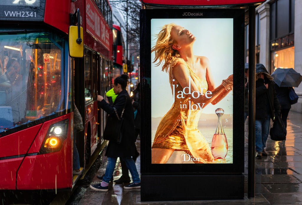 People boarding a double decker bus in central London at a bus stop with a digital advertising display showing an advertisement for a Dior fragrance