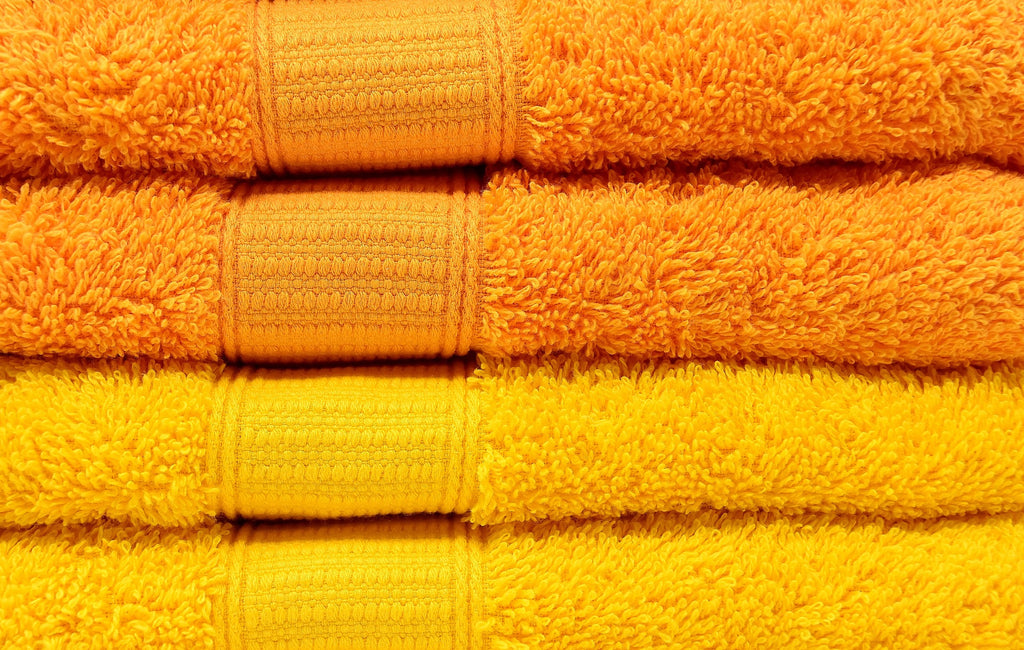 close up of folded orange and yellow towels