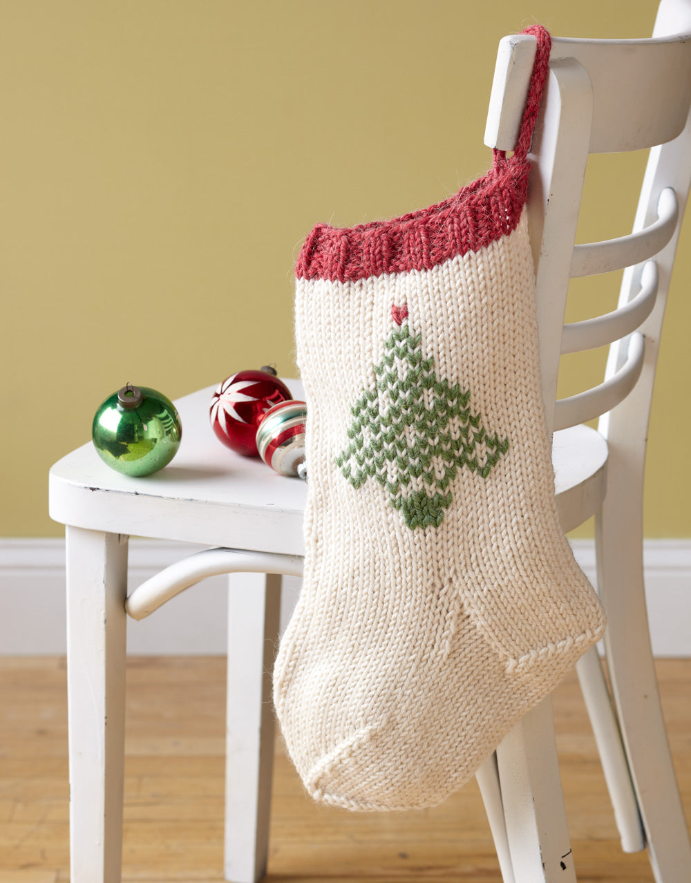 Chunky knit Christmas stocking pattern with colorful tree design using duplicate stitch.