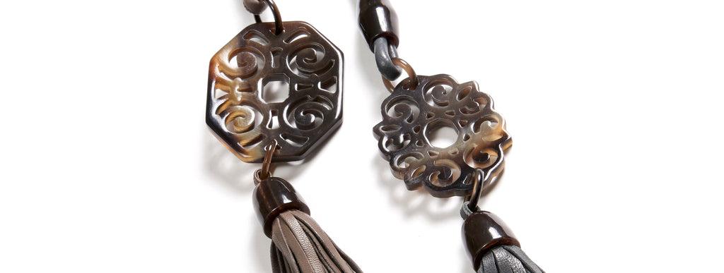 Elsa and Sandra necklaces: Carved buffalo horn rectangular and floral Artdeco pendants. Adjustable Nappa leather bands and tassels.
