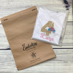 Easterkins eco friendly packaging showing a paper mailing bag which is ocean friendly and plastic free and an organic unicorn birthday T-shirt in a compostable garment bag to protect it.