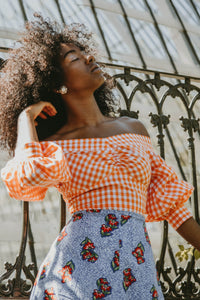 Model wears a puff sleeved off-the-shoulder blouse with an orange vichy print.
