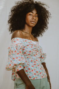 Model wears a puff sleeved off-the-shoulder blouse with a floral print.