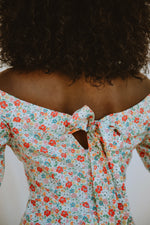 Load image into Gallery viewer, Model wears a puff sleeved off-the-shoulder blouse with a floral print.