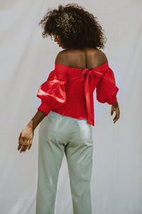 Model wears a puff sleeved off-the-shoulder blouse in red broderie anglaise.