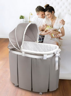 gray bassinet with white ribbon