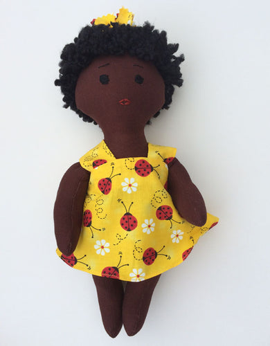 Dark brown African-American baby doll in yellow dress